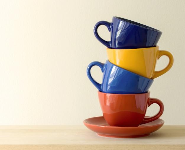 Pila de tazas de café de colores sobre la mesa Foto gratis