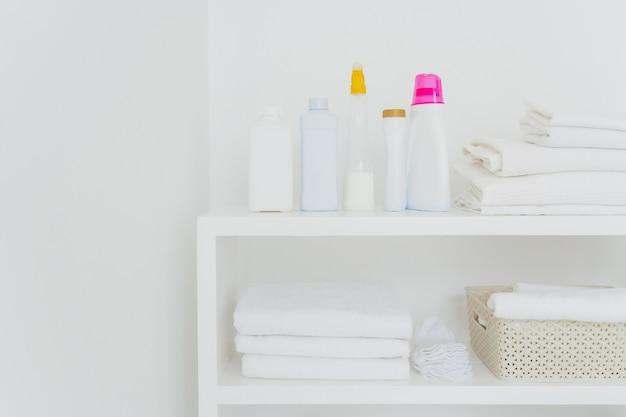 Pila de toallas blancas limpias con detergentes en la consola aislada. lavado fresco y lavado líquido en el baño. Foto Premium