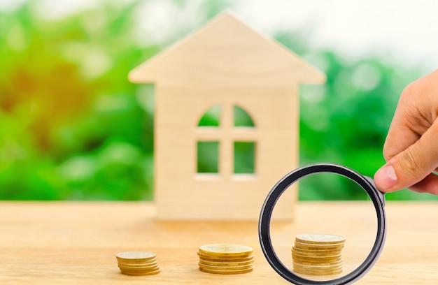 Pilas de monedas y una casa de madera. Foto Premium