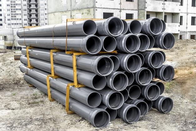 Pilas de tubo de plástico gris en un sitio de construcción.