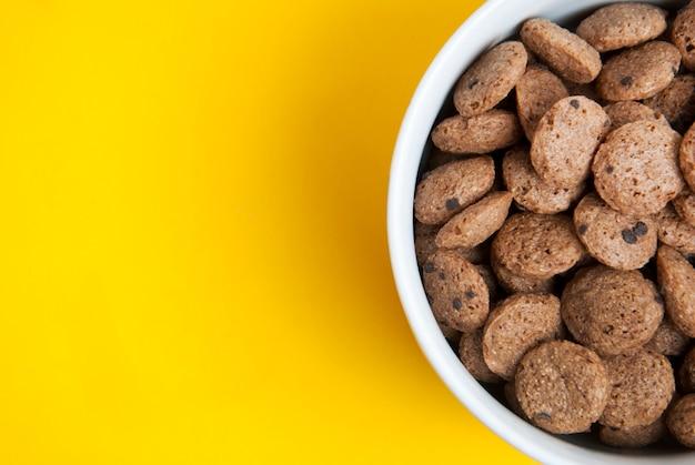 Píldoras del chocolate del desayuno en fondo amarillo. Foto Premium
