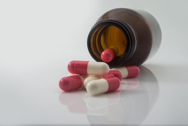 Píldoras médicas que se derraman fuera de un derribado de la botella de píldora Foto gratis
