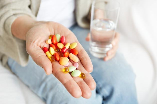 Píldoras, tabletas, vitaminas y medicamentos se amontonan en manos maduras Foto gratis