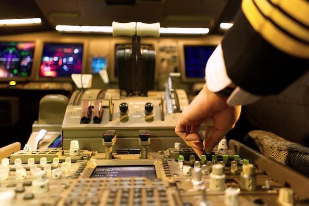 Piloto en uniforme en cabina de avión está sintonizando el panel de radio. Foto Premium