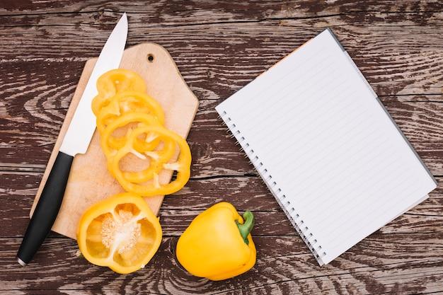 Pimiento amarillo entero y cortado en tabla de cortar con cuchillo y bloc de notas en espiral en el escritorio de madera Foto gratis