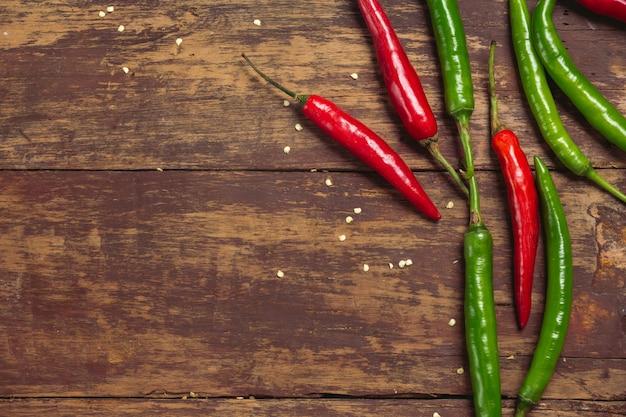 Pimientos jóvenes rojos y verdes colocados en un viejo tablón rojo Foto gratis