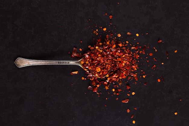 Pimientos secos picados en una cuchara de hierro esparcidos sobre un negro. copyspace Foto Premium