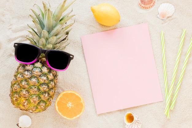 Piña con gafas de sol y papel sobre arena. Foto gratis