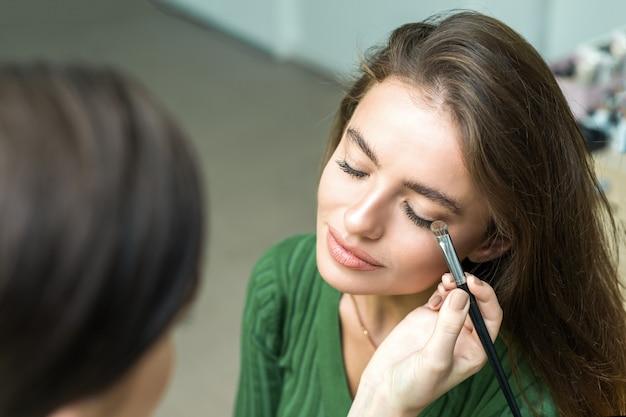 Pincel aplicando maquillaje beige Foto Premium