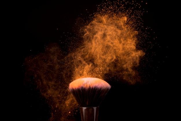 Pincel de maquillaje con partículas voladoras de polvo ligero. Foto gratis