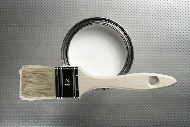 Pincel para pintor y lata de pintura blanca. Foto Premium