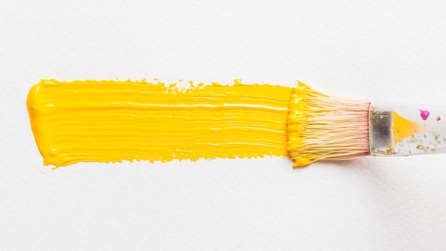 Pincel de pintura con color amarillo Foto gratis