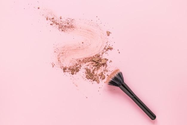 Pincel en polvo con polvo desmenuzado esparcido sobre la mesa Foto gratis