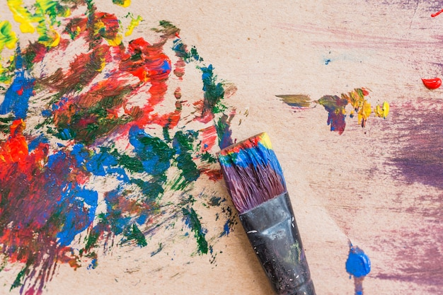 Pincel sucio viejo y superficie pintada desordenada multicolor Foto gratis