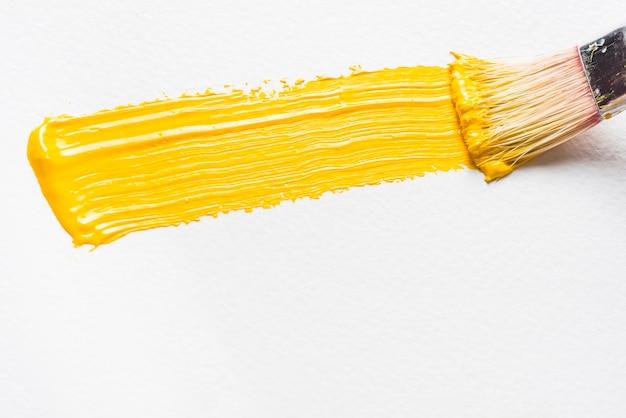 Pincel y trazo de pintura amarilla Foto gratis