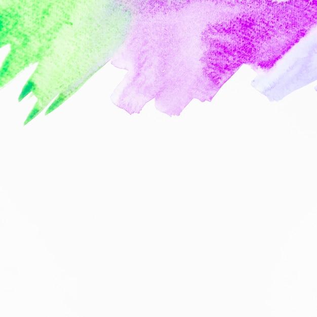 Pincelada de acuarela verde y púrpura sobre fondo blanco Foto gratis