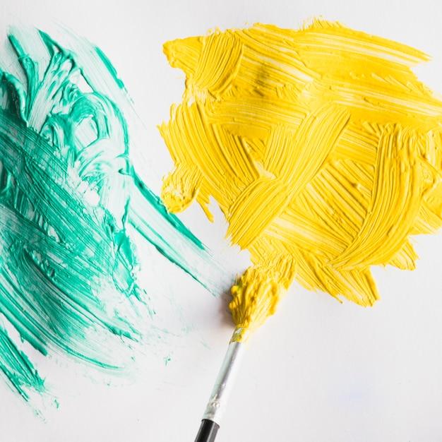 Pincelada de pintura verde y amarillo en hoja de papel blanco Foto gratis