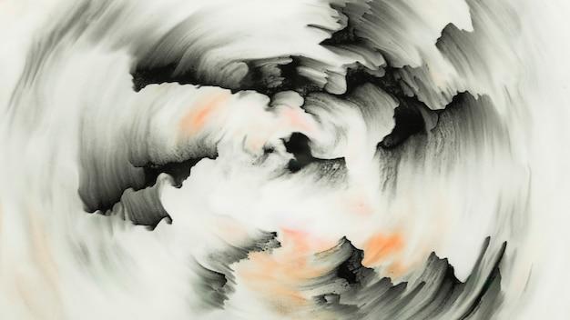 Pinceladas de color negro que forman una forma circular sobre una superficie blanca Foto gratis