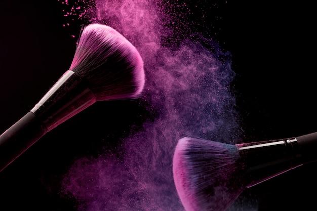 Pinceles cosméticos y polvo de maquillaje sobre fondo oscuro Foto gratis