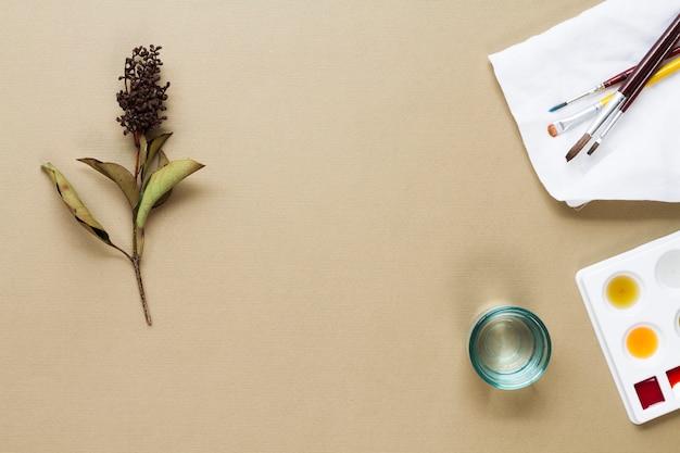 Pinceles con paleta de acuarela y flor. Foto gratis