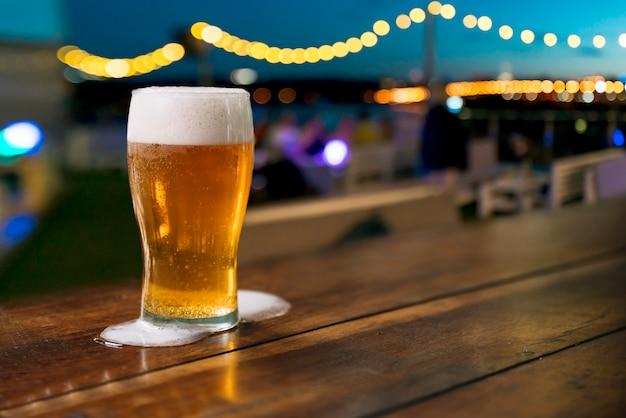 Pinta de cerveza con espuma derramada. Foto Premium