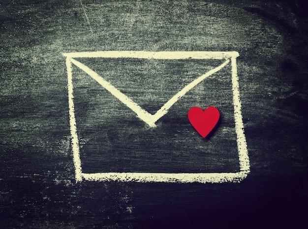 Pintado sobre con el corazón rojo en una pizarra. vista superior. amor; Foto gratis