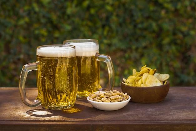 Pintas de alto ángulo con cerveza y aperitivos en la mesa Foto gratis