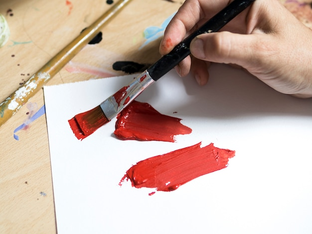 Pintor de alto ángulo con pintura roja en primer plano de pincel Foto gratis