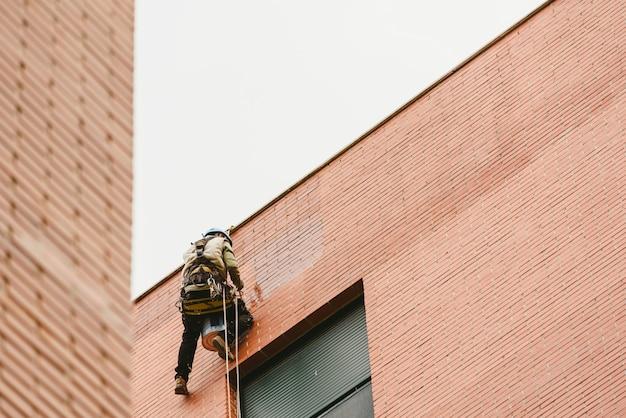 Pintor escalador suspendido de cuerdas y arneses pinta el exterior de un edificio de apartamentos Foto Premium