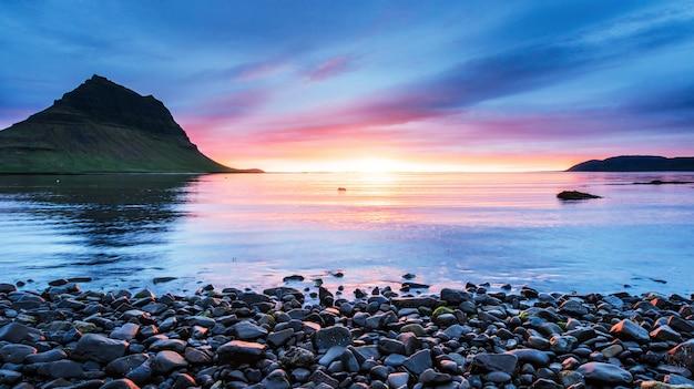 La pintoresca puesta de sol sobre paisajes y cascadas. montaña kirkjufell, islandia Foto Premium