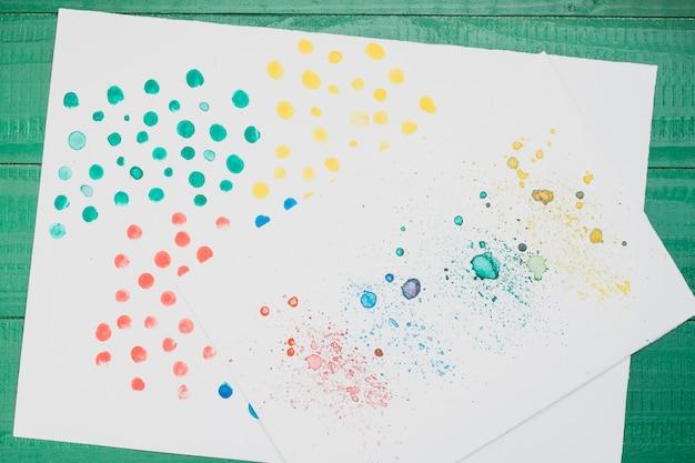 Pintura abstracta manchada multicolor sobre papel blanco sobre mesa verde Foto gratis