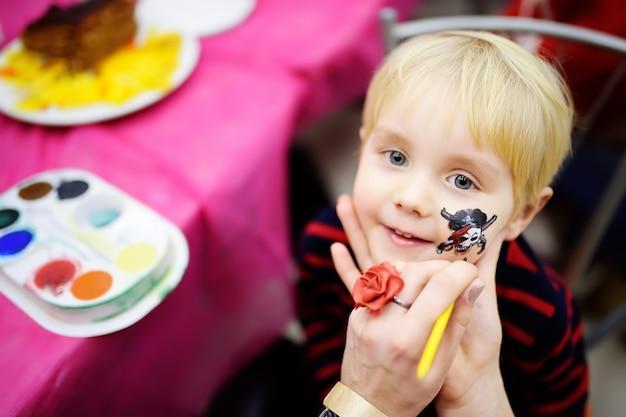 Pintura de la cara para el niño pequeño lindo durante la fiesta de cumpleaños de los niños Foto Premium