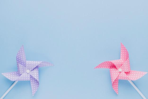 Pinwheel de origami púrpura y rosa sobre fondo azul claro Foto gratis