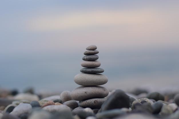 Una pirámide de piedras de diferentes tamaños en la costa del mar negro Foto Premium