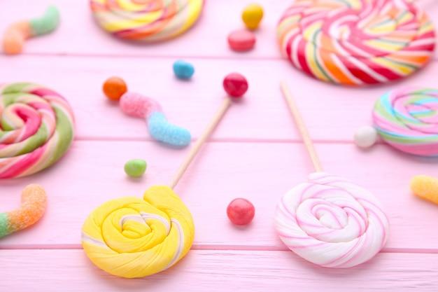Piruletas de colores y dulces redondos de diferentes colores sobre fondo de madera rosa Foto Premium