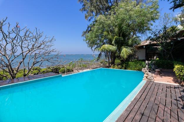 Piscina de agua azul y jardín tropical con fondo de vista al mar. Foto gratis