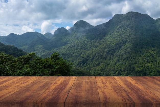 Piso de madera marrón con montaña verde. Foto gratis