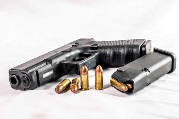 Pistola de 9 mm y balas esparcidas con municiones sobre fondo de madera Foto Premium