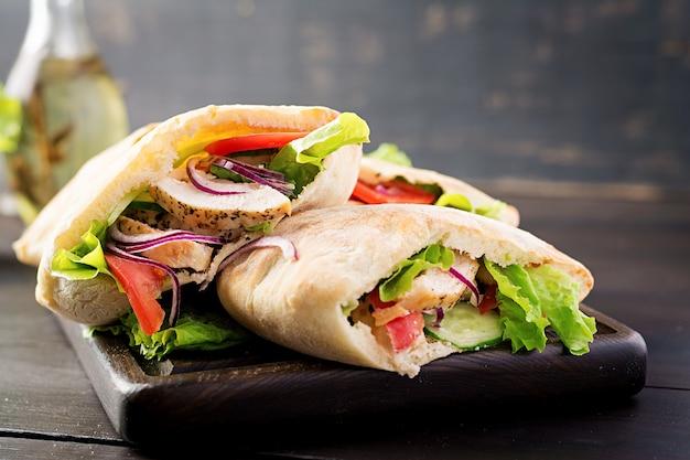 Pita rellena de pollo, tomate y lechuga en la mesa de madera. cocina del medio oriente. Foto gratis