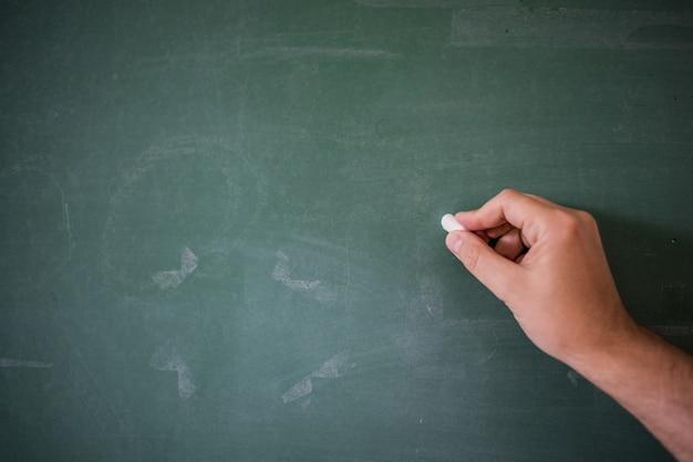 Pizarra en blanco / pizarra, la escritura de la mano en tiza verde tiza sosteniendo la tiza, gran textura para el texto. Mano del profesor que sostiene la tiza delante de la pizarra en blanco. Escritura de la mano con el copyspace para el texto. Buena textura. Foto Gratis