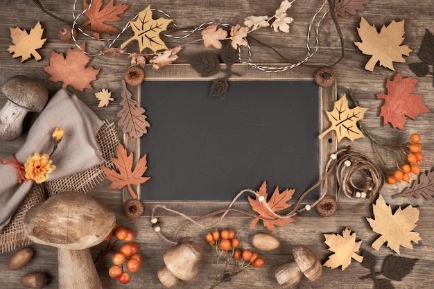 Pizarra enmarcada con decoraciones otoñales en espacio de madera Foto Premium