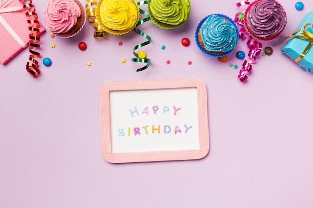 Pizarra de feliz cumpleaños con gemas de colores; serpentinas y muffins sobre fondo rosa Foto gratis