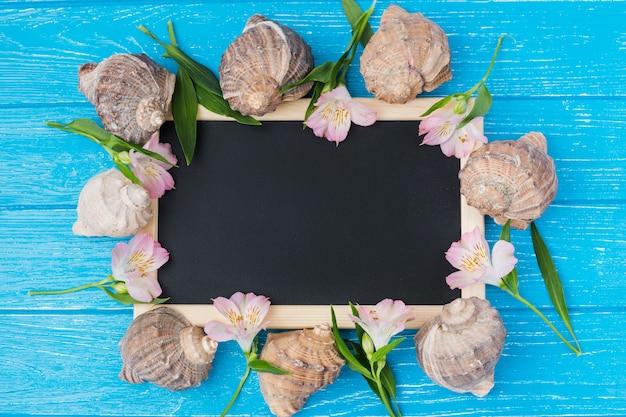 Pizarra con hojas de la planta y flores en el escritorio Foto gratis