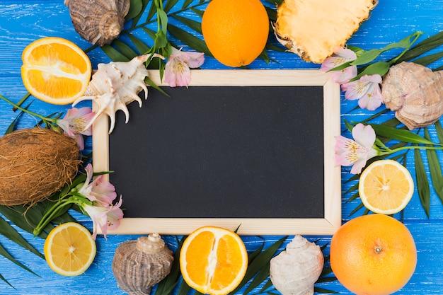 Pizarra entre las hojas de la planta con frutas y flores en el escritorio Foto gratis