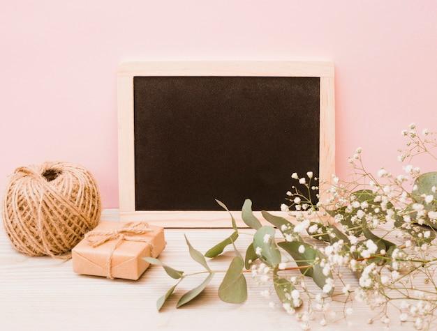 Pizarra de madera en blanco con carrete; caja de regalo y flores de aliento de bebé en el escritorio de madera con fondo rosa Foto gratis