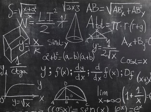 Pizarra negra con fórmulas matemáticas y problemas. Foto gratis