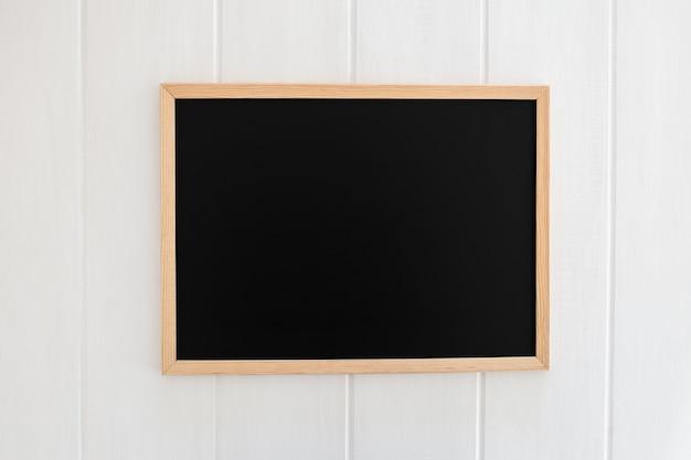 Pizarra negra sobre fondo blanco de madera Foto gratis