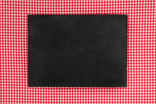 Pizarra plana vacía sobre tela roja Foto gratis