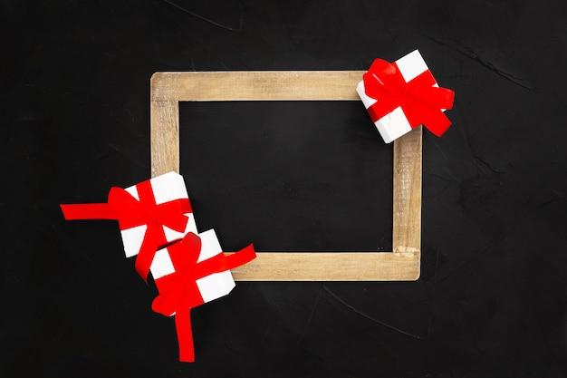 Pizarra con regalos de navidad sobre fondo negro Foto gratis