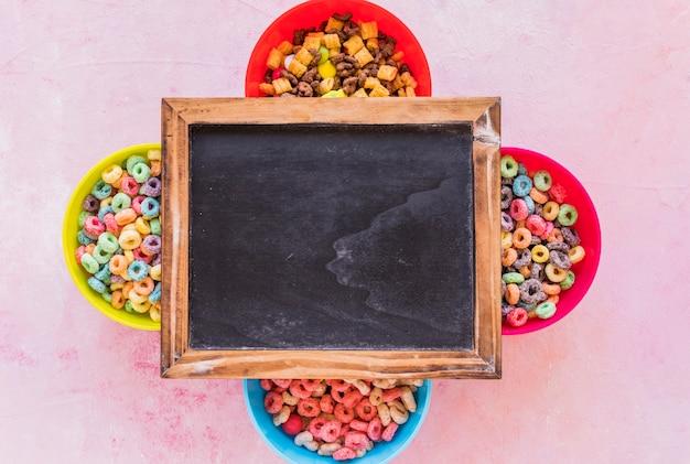 Pizarra sobre cuatro tazones de cereales. Foto gratis